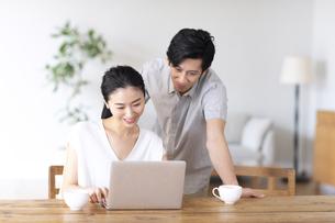 部屋でノートパソコンをしながら会話する夫婦の写真素材 [FYI04089056]
