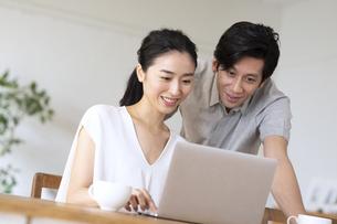 部屋でノートパソコンをしながら会話する夫婦の写真素材 [FYI04089057]