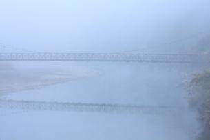 霧に包まれ川面に映る吊り橋の写真素材 [FYI04089876]