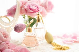 クラシックな形の香水瓶とピンクのバラの花の写真素材 [FYI04089948]