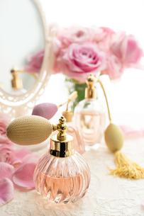 クラシックな形の香水瓶とピンクのバラの花の写真素材 [FYI04089949]