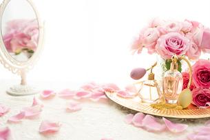 クラシックな形の香水瓶とピンクのバラの花の写真素材 [FYI04089950]