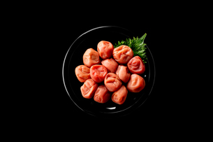 Umeboshi,Japanese salt plums on black plate. Traditional Japanese food.の写真素材 [FYI04090292]
