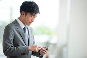 スマートフォンを操作するビジネスマンの写真素材 [FYI04091820]