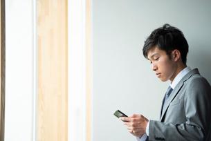 スマホを操作するビジネスマンの写真素材 [FYI04091836]