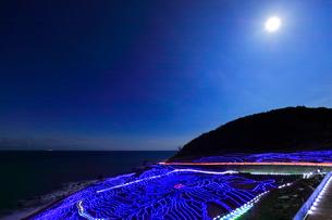 冬の能登半島 白米千枚田あぜのきらめきと夜空に月の写真素材 [FYI04092386]