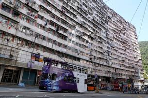 トランスフォーマーのロケ地にもなった香港はクウォリーベイのモンスターマンション海景楼前を走るトラムの写真素材 [FYI04092591]