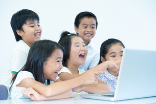 ノートPCを見て笑う五人の小学生の写真素材 [FYI04092659]
