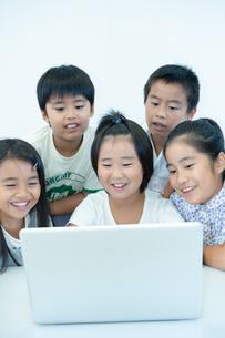 ノートPCを見て笑う五人の小学生の写真素材 [FYI04092661]