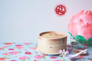 花柄クロスの上の蒸籠と花飾りの写真素材 [FYI04093226]