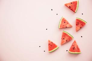 ランダムに置いたスイカと種とピンクの背景の写真素材 [FYI04093593]