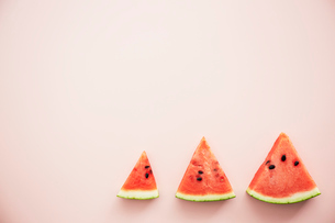 大中小のスイカとピンクの背景の写真素材 [FYI04093595]