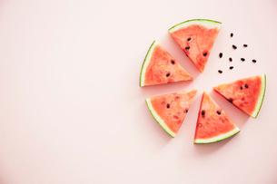 丸に並べたスイカと種とピンクの背景の写真素材 [FYI04093597]