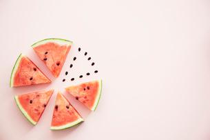 丸に並べたスイカと種とピンクの背景の写真素材 [FYI04093599]