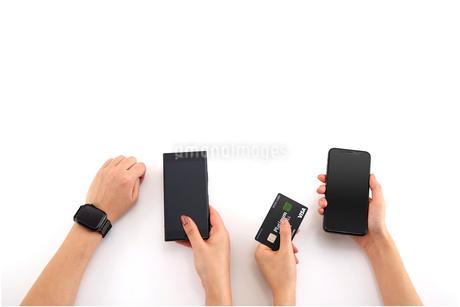 スマホとクレジットカードを持つ男女の手元の写真素材 [FYI04093765]