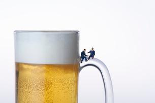 ビールジョッキの取っ手に座るスーツ姿のミニチュア人形の写真素材 [FYI04094324]