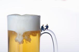 ビールジョッキの取っ手に座るスーツ姿のミニチュア人形の写真素材 [FYI04094325]