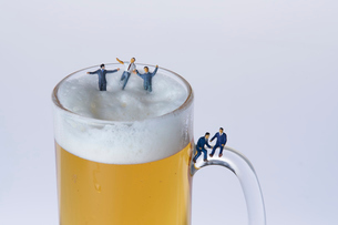 ビールジョッキとスーツ姿のミニチュア人形の写真素材 [FYI04094326]