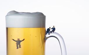 ビールジョッキとスーツ姿のミニチュア人形の写真素材 [FYI04094327]