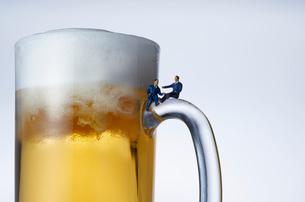 ビールジョッキの取っ手に座るスーツ姿のミニチュア人形の写真素材 [FYI04094328]
