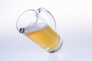 傾いたビールジョッキの縁に座るスーツ姿のミニチュア人形の写真素材 [FYI04094334]
