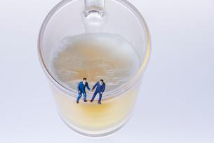 ビールジョッキの縁に座るスーツ姿のミニチュア人形の写真素材 [FYI04094335]