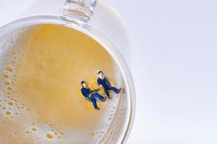 ジョッキのビールに溺れるスーツ姿のミニチュア人形の写真素材 [FYI04094336]