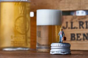 グラスのビールと瓶の蓋に立つスーツ姿のミニチュア人形の写真素材 [FYI04094337]