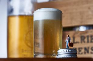 グラスのビールと瓶の蓋に立つスーツ姿のミニチュア人形の写真素材 [FYI04094338]