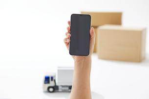 運送のトラックとスマートフォンを持つ手の写真素材 [FYI04094409]