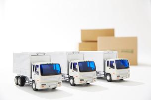 3台並ぶ運送のトラックと段ボールの写真素材 [FYI04094410]
