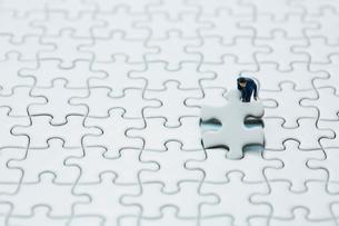 真っ白なパズルの1ピースをはめるスーツ姿のミニチュア人形の写真素材 [FYI04094423]