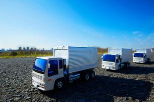 広い青空と道に3台並ぶおもちゃのトラックの写真素材 [FYI04094431]