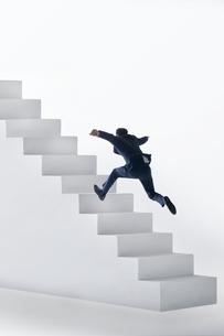白い階段を上るスーツ姿の男性の後ろ姿の写真素材 [FYI04094575]