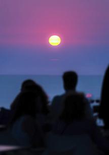 エーゲ海に見る夕日と人々のシルエットの写真素材 [FYI04094973]