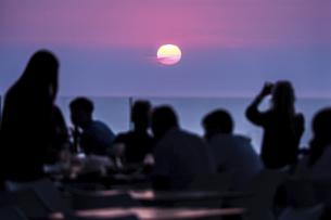 エーゲ海に見る夕日と人々のシルエットの写真素材 [FYI04094974]