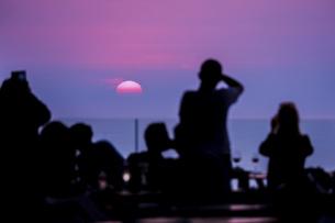 エーゲ海に沈む夕日と人々のシルエットの写真素材 [FYI04094975]