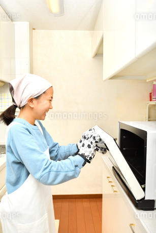 キッチンで料理をする女の子の写真素材 [FYI04095201]
