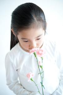 カーネーションの香りをかぐ女の子の写真素材 [FYI04095342]