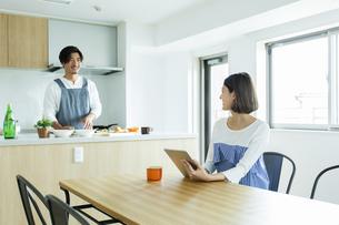 朝食の準備をする日本人男性とタブレットPCを持つ日本人女性の写真素材 [FYI04095757]
