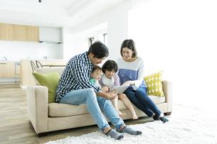 タブレットPCを見る日本人家族4人の写真素材 [FYI04095825]