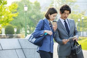 タブレットPCを見るビジネスマンとビジネスウーマンの写真素材 [FYI04095839]