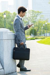 スマートフォンを見るビジネスマンの写真素材 [FYI04095861]