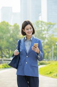 スマートフォンを見るビジネスウーマンの写真素材 [FYI04095871]