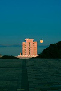 シンボルプロムナード公園から見る満月と夕日に輝くビルの写真素材 [FYI04096421]