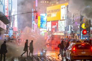 吹雪の夜にタイムズスクエアのイルミネーションに照らされ輝き漂う蒸気の中を行き交う人々と交通の写真素材 [FYI04096953]