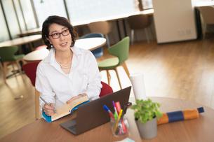 シェアオフィスで手帳にメモをとる女性の写真素材 [FYI04098798]