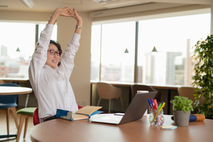 シェアオフィスで伸びをする女性の写真素材 [FYI04098799]