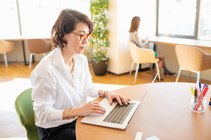 シェアオフィスでノートPCを操作する女性の写真素材 [FYI04098832]