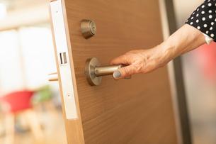扉を開ける女性の手元の写真素材 [FYI04098843]